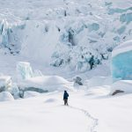 Chris Kassar takes a walk near a few icebergs next to the Triumvirate Glacier. During summer, a lake sometimes forms here and drains in a dramatic rush of water from time to time. Photo: Colin Wiseman.