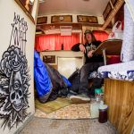 "Chris Curran aka ""Blood"" from Revelstoke's Wasted Youth crew, poses in their Bigfoot camper, which was freshly painted by Jamie Lynn."
